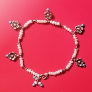 Artisan anklet with beads and flower pendants